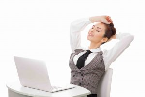 Young attractive woman at modern office desk, with laptop, stretching, getting a little exercise during the day, completing difficult task time for lunch. Businesswoman against white isolated background. Business concept illustration.