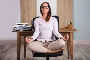 Young Businesswoman Sitting On Chair Meditating In Office